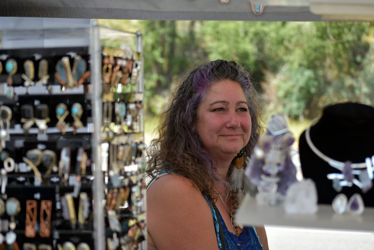 Shelly Birch waits to answer customers' questions about her handmade stone jewelry at her booth at Art in the Park in Steamboat Springs on Sunday.