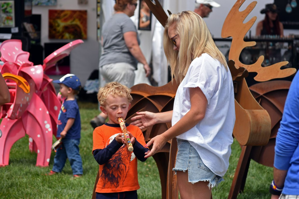 Kaeden Campbell plays a recorder with help from family friend Kathryn Smith at Art in the Park in Steamboat Springs on Sunday.