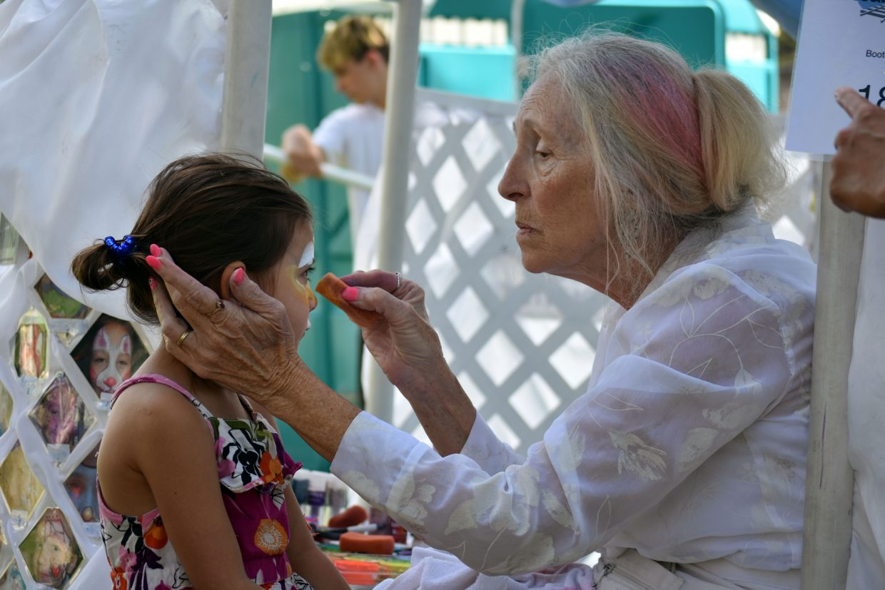 Marshmallows & Clouds face-painting artist Linda Zimmerman paints Xyriel Law's face at Art in the Park in Steamboat Springs on Sunday.