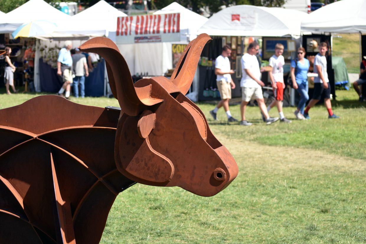 A nodding longhorn statue sits in the middle of Art in the Park in Steamboat Springs on Sunday.