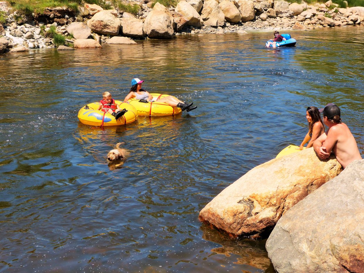 Tubers and dogs enjoy time in the Yampa River.