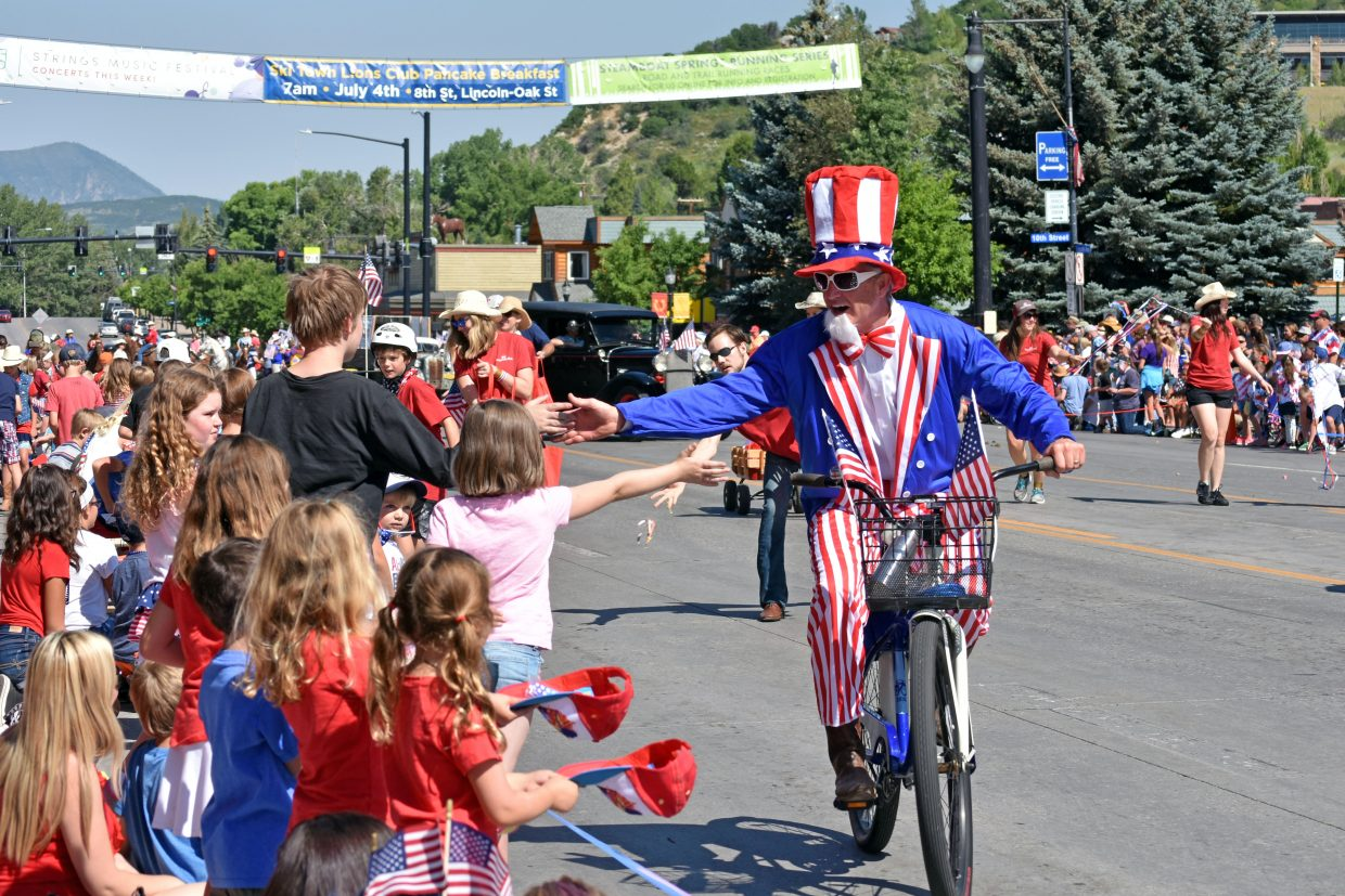 Uncle Sam gives children high fives on Lincoln Avenue during Steamboat's Fourth of July parade Wednesday morning.