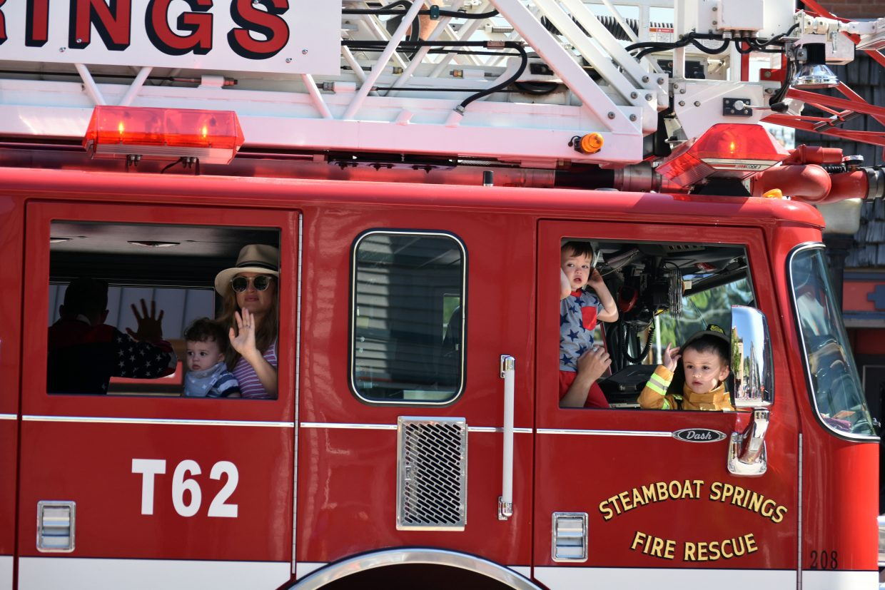 Children wave from a Steamboat Springs Fire Rescue fire engine in Steamboat's Fourth of July parade Wednesday morning.