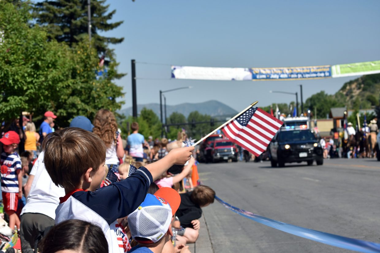 A child waves a flag as Steamboat's Fourth of July parade begins Wednesday morning.