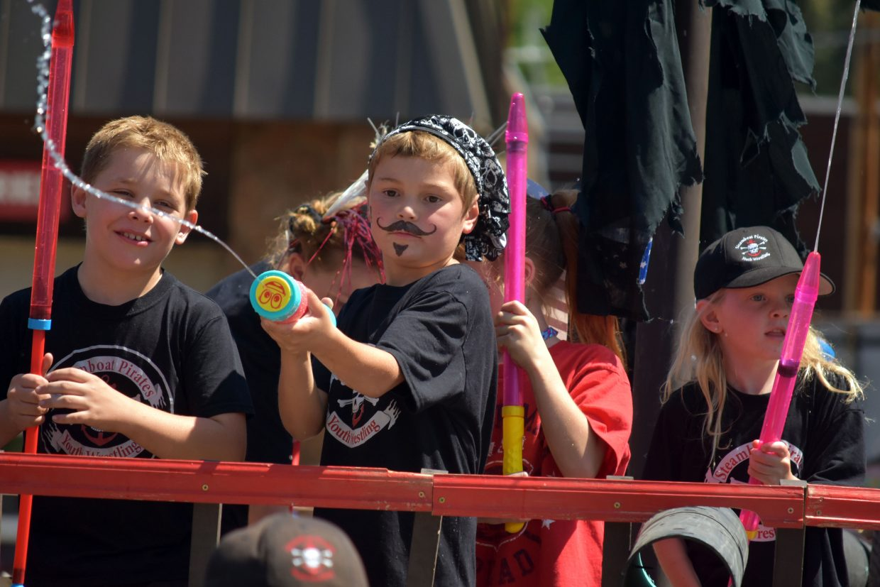 A member of Steamboat Pirate Wrestling uses a water gun to soak spectators during Steamboat's Fourth of July parade Wednesday morning.