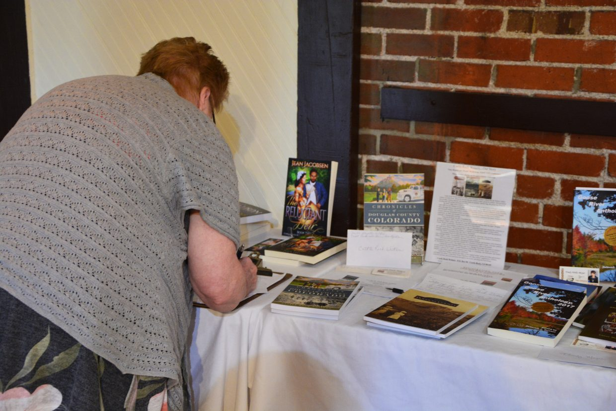Jean Jacobsen, one of the many published writers present, sets up her books to be sold after the conference concludes.