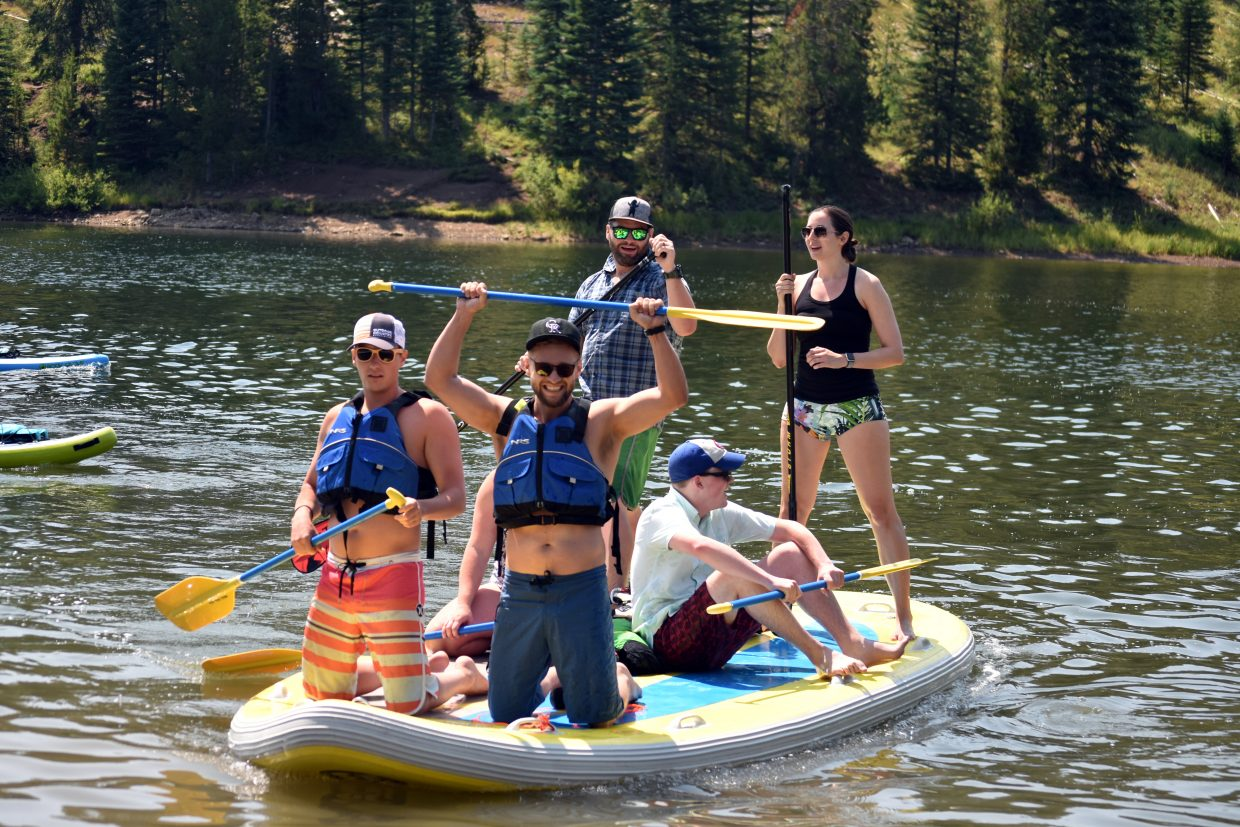 A group on the SUPsquatch, a mega paddleboard, celebrate finishing the open class race at the Pearl Lake Festival on Saturday.
