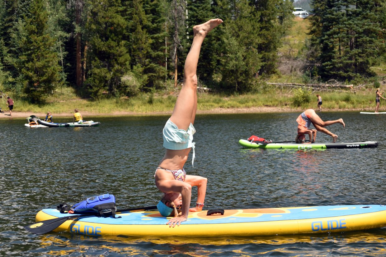 Courtney Tebbenkamp balances in a headstand while participating in paddleboard yoga at the Pearl Lake Festival on Saturday.