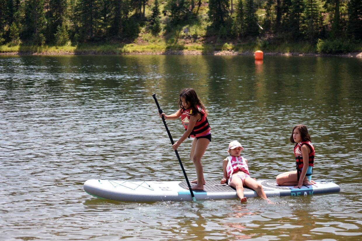 Children float on a paddle board at the Pearl Lake Festival on Saturday.