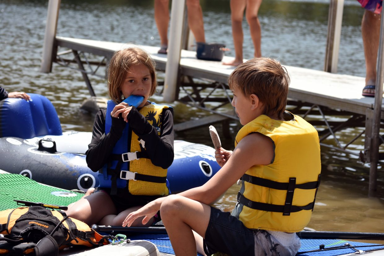 Children eat paletas on paddleboards sitting ashore at the Pearl Lake Festival on Saturday.