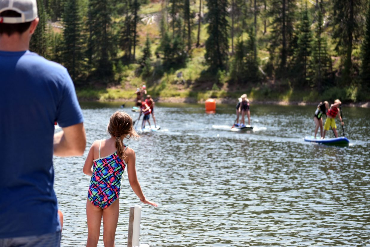 Spectators watch as racers compete in a tandem paddleboard race at the Pearl Lake Festival on Saturday.
