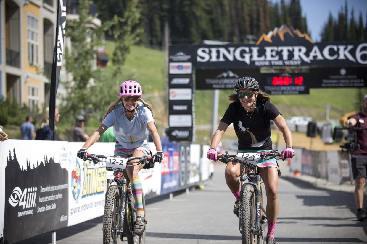 Karen Tremaine (left) and Mindy Mulliken (right) ride their final day of the Singletrack 6 in their unicorn attire.