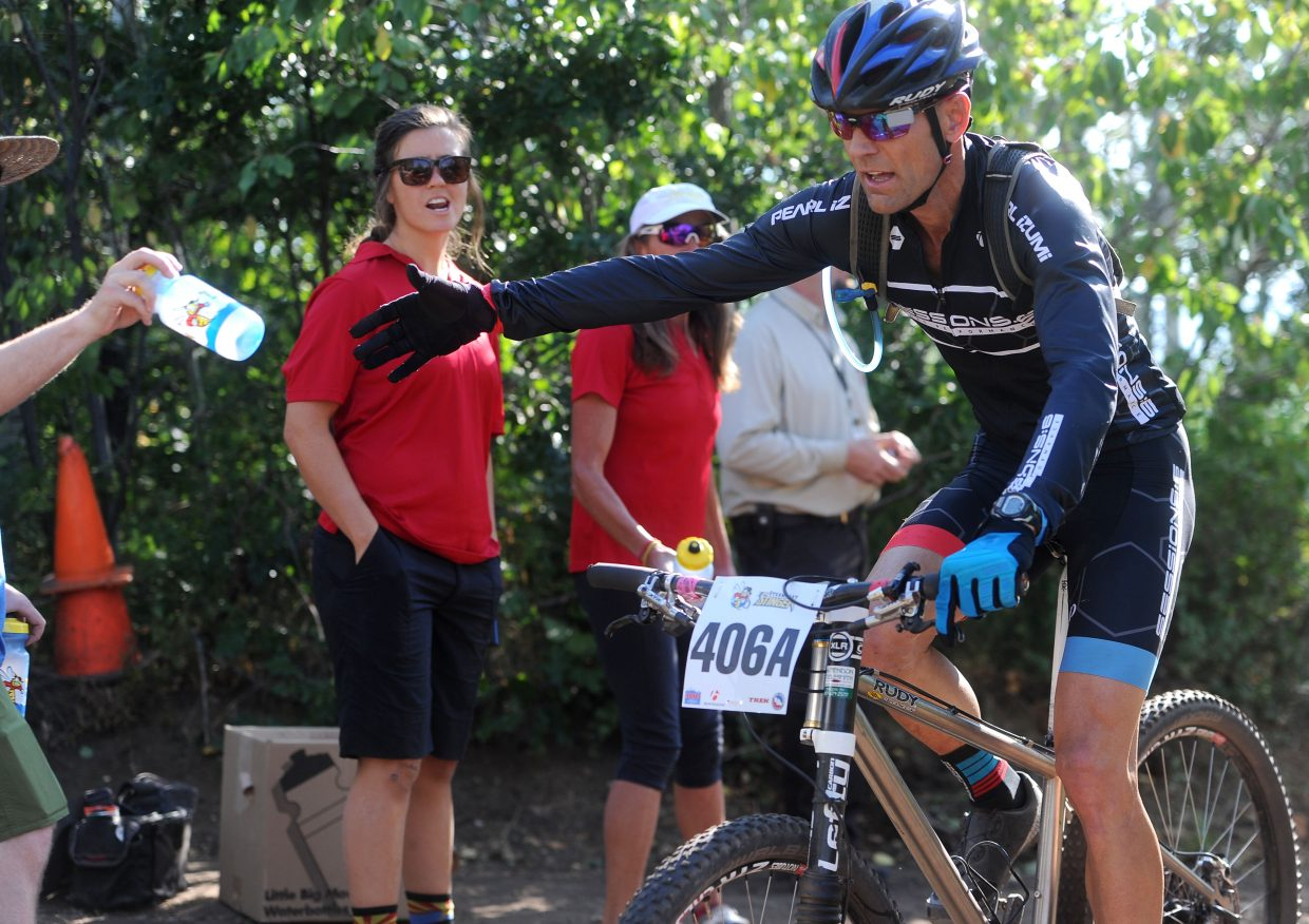 Rick Zimmerman grabs a water bottle at the aid station on Ridge Trail at Saturday's Steamboat Stinger.