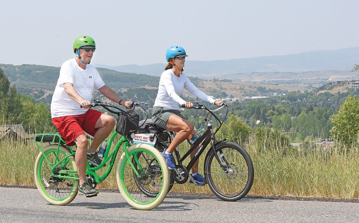 Steve and Brenda Dawes make their way up Blue Sage Drive on pedal-assist bikes in 2018. Steamboat Springs Parks and Recreation Commission is favoring a one-year trail period to allow e-bikes on soft surface trails in the city. Current policies restrict the bikes to paved trails.
