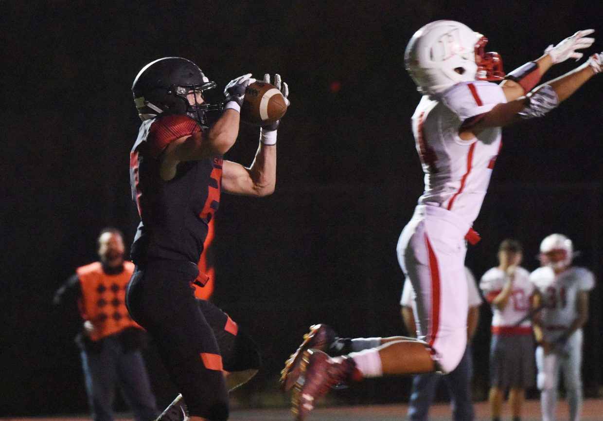 Steamboat's Tanner Raper pulls in a touchdown pass, his second of the game, Friday despite a leaping Hotchkiss defense.