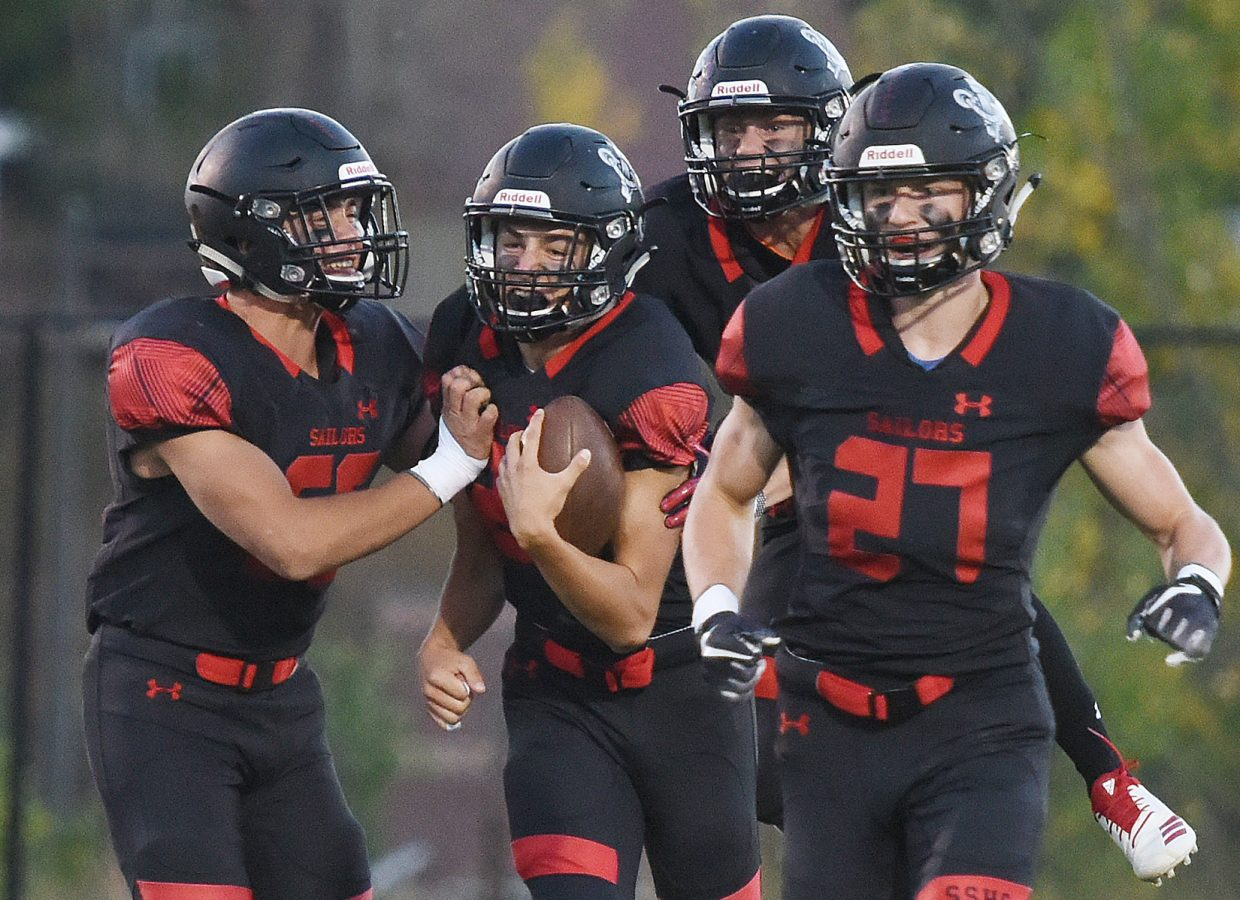 Steamboat sophomore Jameson Terry, second from left, is mobbed by his teammates after returning a first-quarter interception for a touchdown on Friday against Hotchkiss.