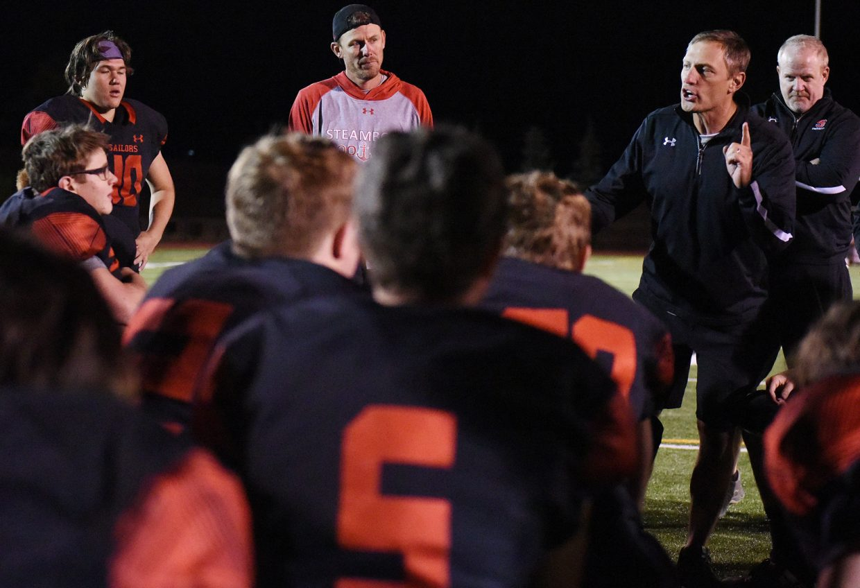Steamboat coach Shawn Baumgartner talks with his team after Friday night's 40-7 win at home against Hotchkiss.