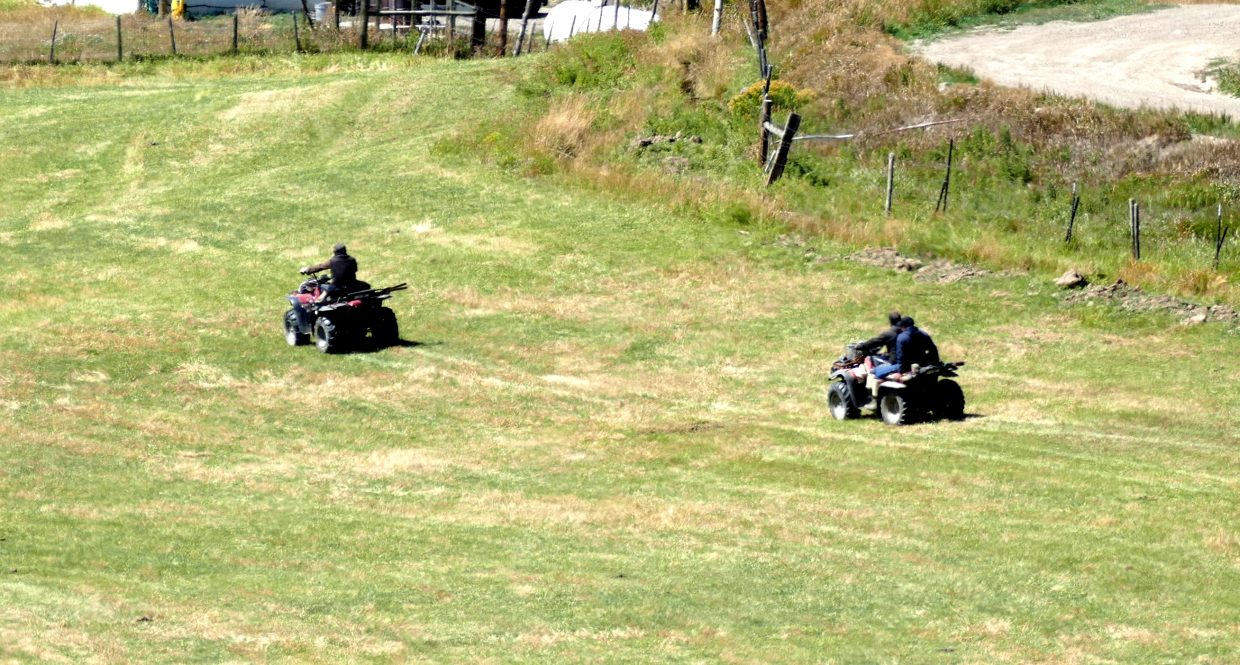 Three people ride four wheelers on at a farm on U.S. Highway 40.