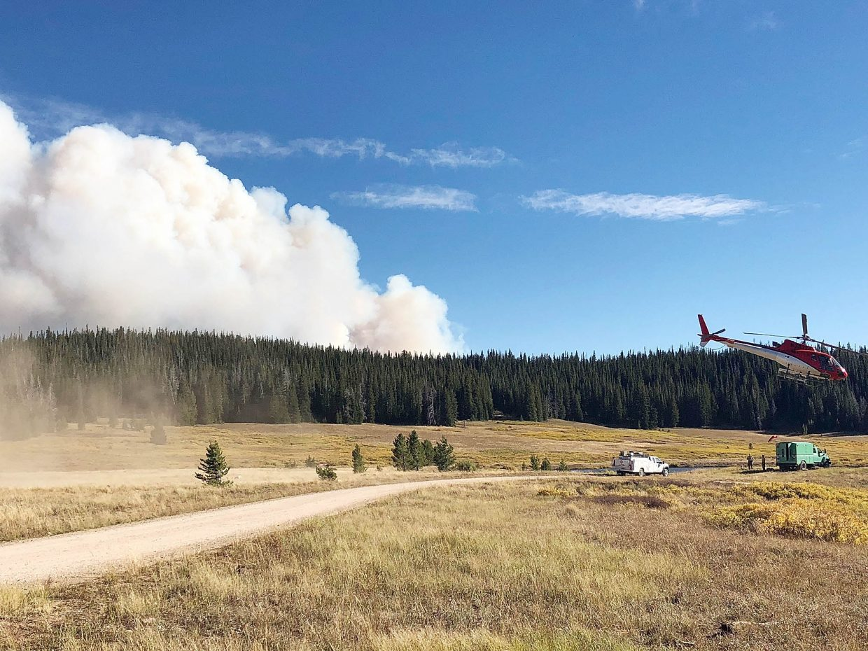 A helicopter takes off Wednesday to drop water on the Silver Creek Fire.
