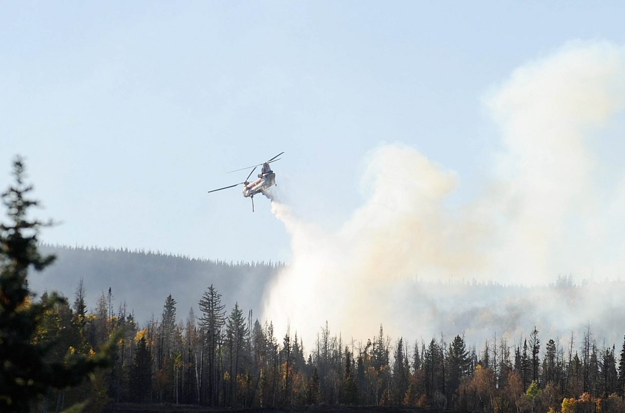 A helicopter drops water on a hot spot at the Silver Creek Fire.