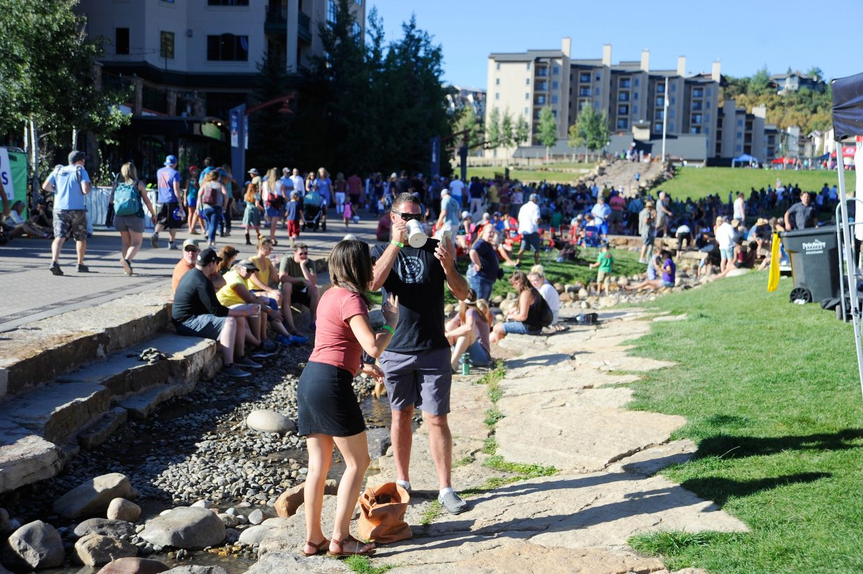 People hang out along Burgess Creek on Saturday during OktoberWest.