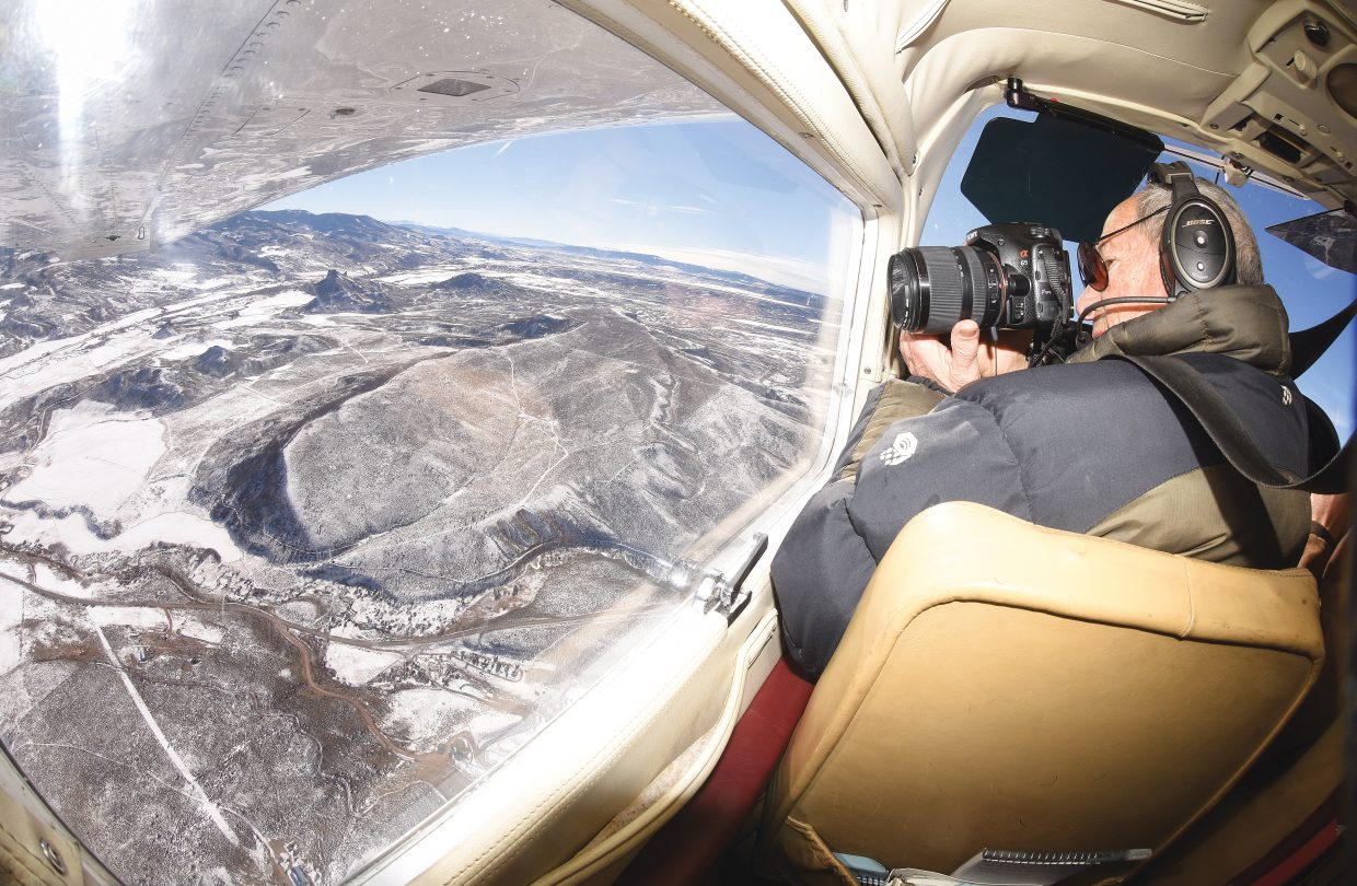 Bruce Gordon, EcoFlight's executive director, takes photos during an aerial tour of the Yampa River Basin high above the South Routt landscape.