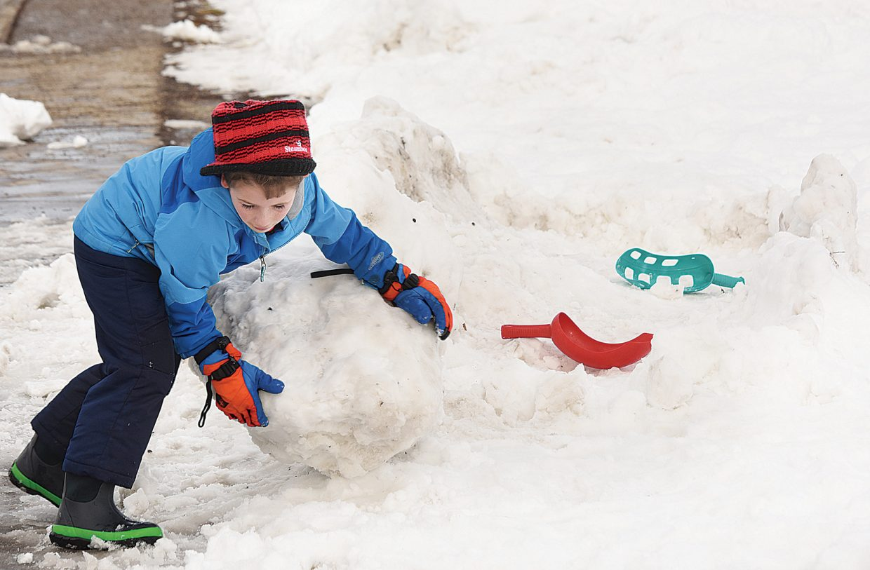 Jake Myrtle pushes a large snowball while building a snow fort in the field in front of the George P. Sauer Human Services Center in downtown Steamboats. Myrtle and his classmates from the Emerald Mountain School spent their recess using the fresh snow from last night's storm.