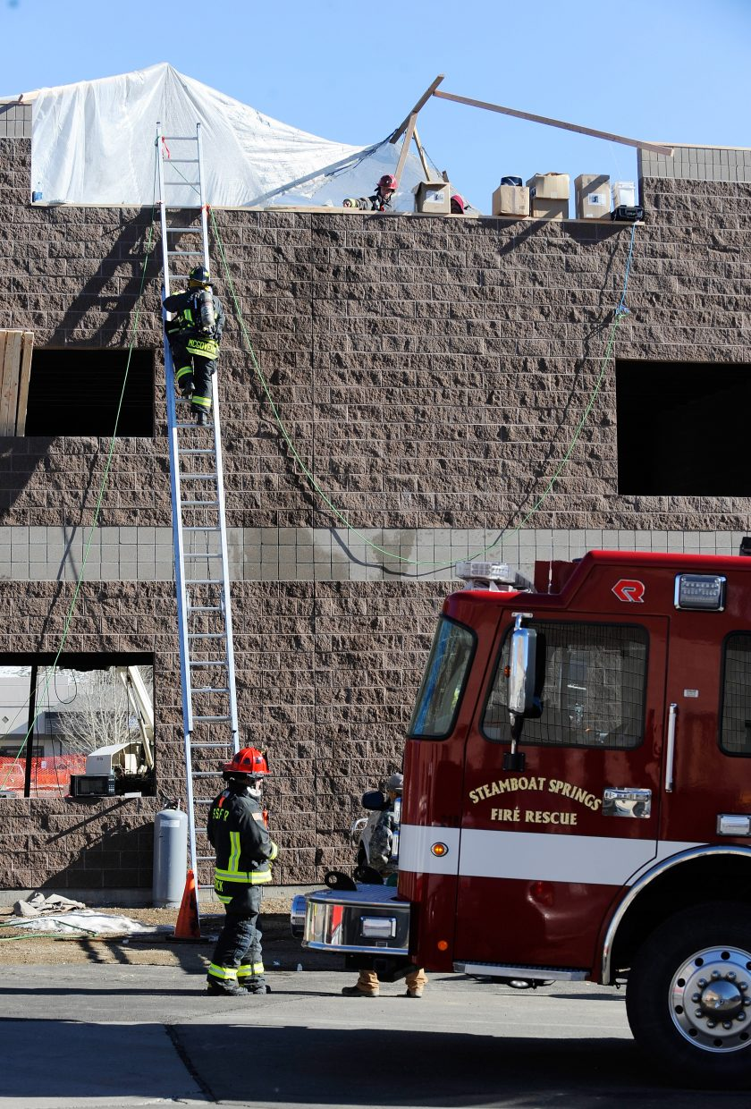 Steamboat Springs Fire Rescue firefighters climb onto the roof of a building under construction off of Downhill Drive on Friday to investigate a fire. The fire was out when they arrived. A 20-foot area of insulation burned. The fire was started by a heater.