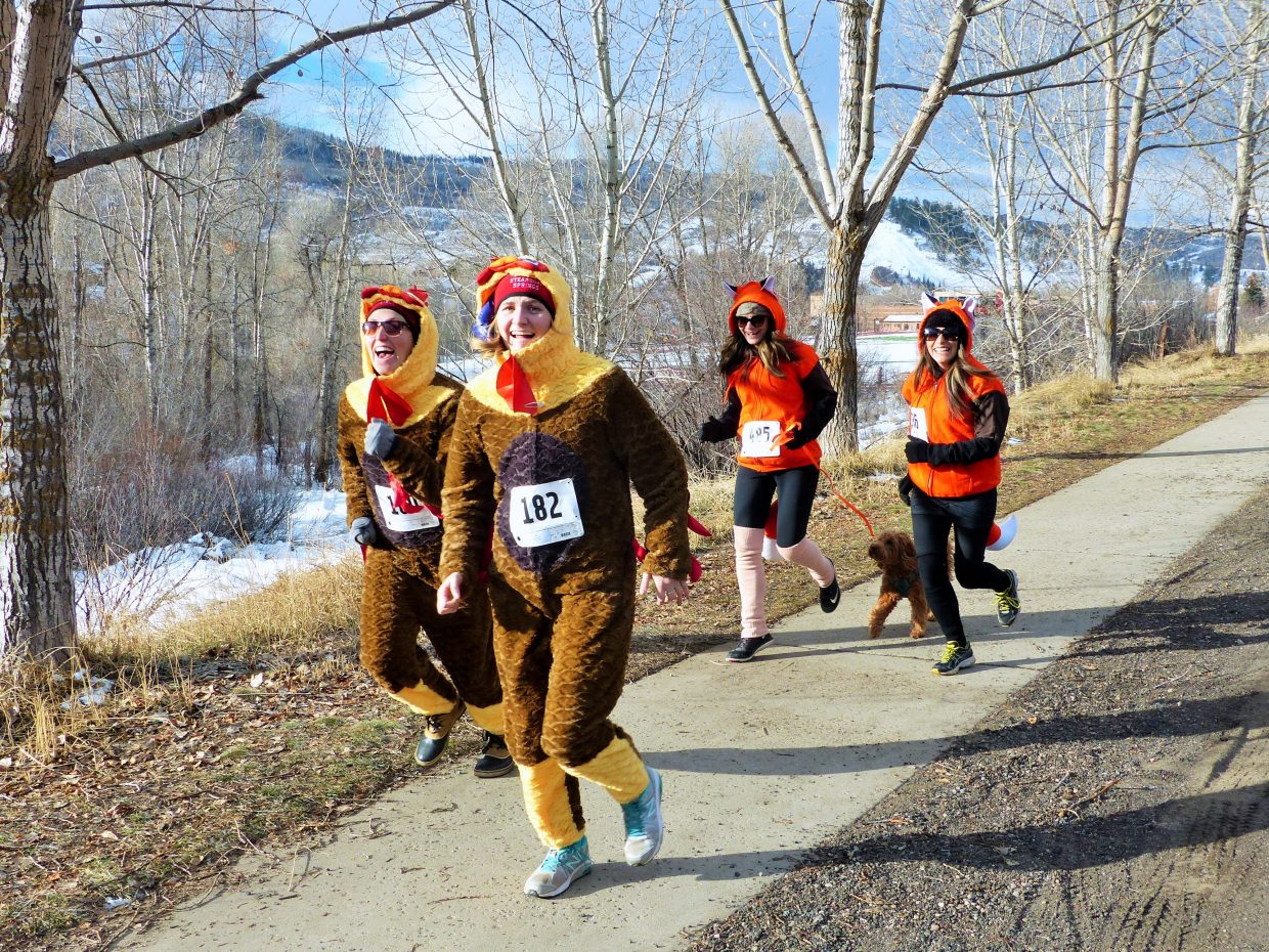 Runner dressed as turkeys and foxes race in the 5-kilometer Turkey Trot, benefitting the Steamboat Springs High School track and cross country teams.