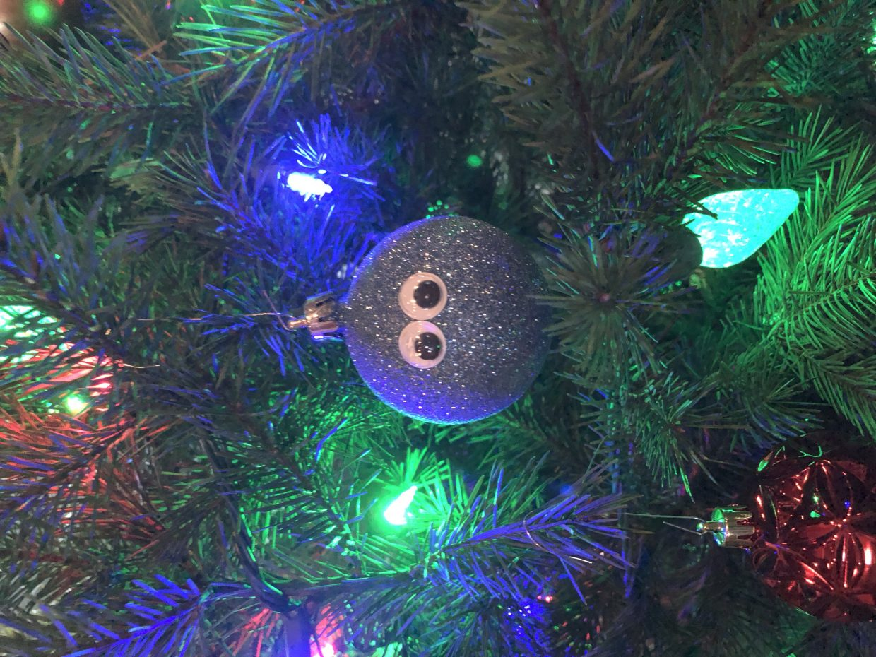 A Christmas ornament peers through the tree limbs.