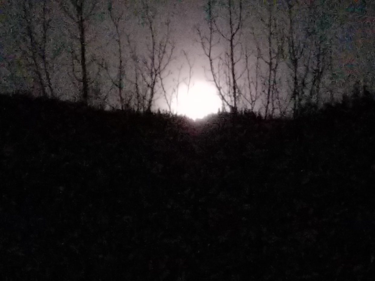 The moon seems to rest on Mount Werner.