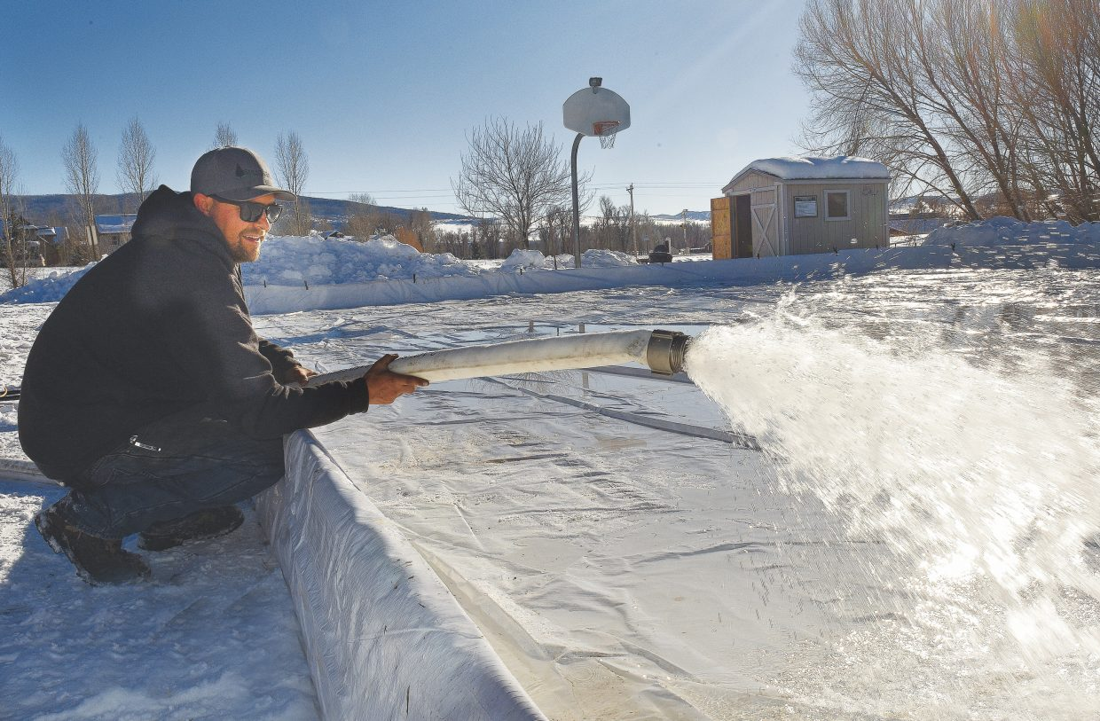 Forrest Hunter, an employee with the Steamboat II Metro District, floods the surface of the neighborhood ice skating rink Thursday. Once the rink is flooded it will take four to five days for the ice surface to freeze completely. The rink will remain closed until then, but should be open soon as long as freezing temperatures continue in the Steamboat Springs area.
