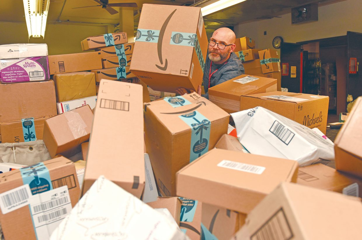 Josh Styron, an employee with the U.S. Postal Service, sorts packages at the Steamboat Springs office Thursday afternoon.  With the holiday rush already in full swing, and the fact the officeÕs doors were closed on Wednesday to honor President George H.W. Bush, it's shaping up to be a really busy month.
