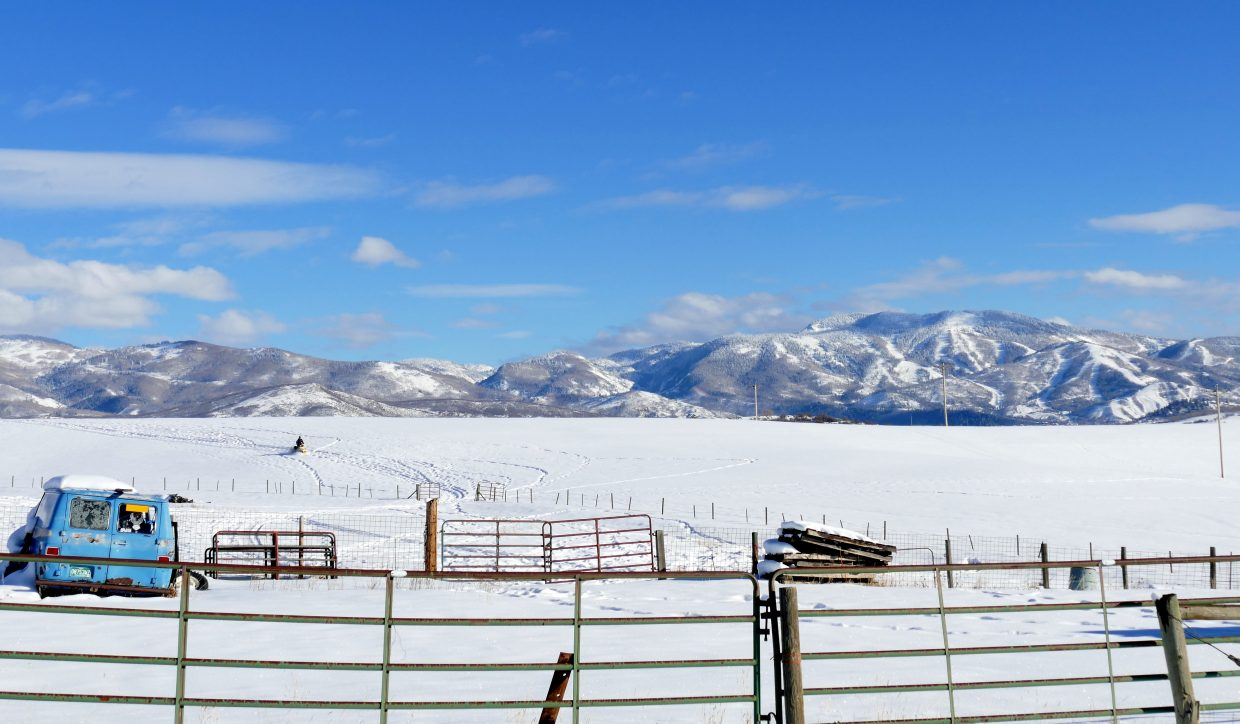 A snowmobiler coming back to his ranch.