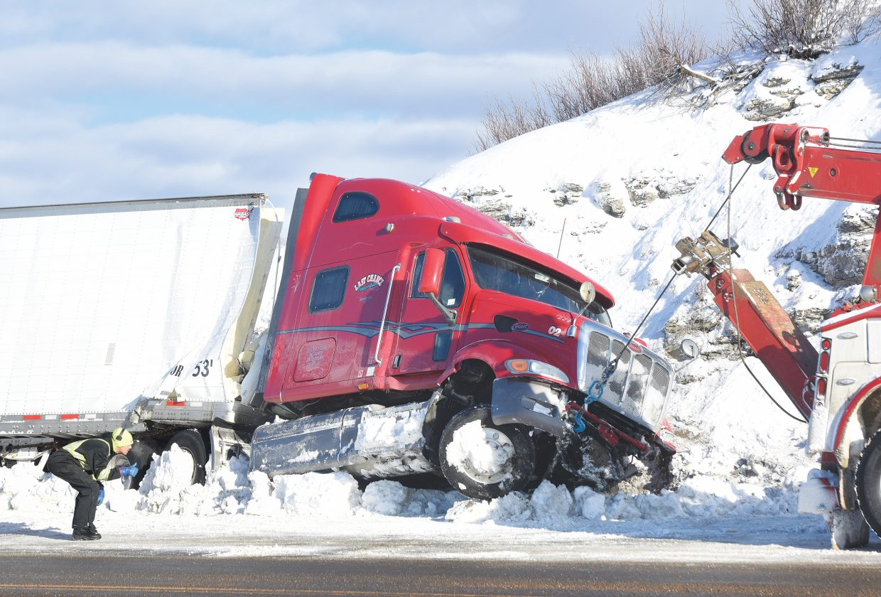 Crews work to tow a truck off the side of the road after a crash on U.S. Highway 40 near the Rifle County Rifle Club on Tuesday.