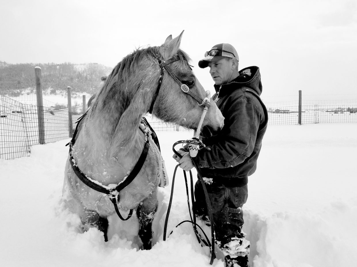 Robert Greenwood working with his horse, Spurs in hip deep powder.