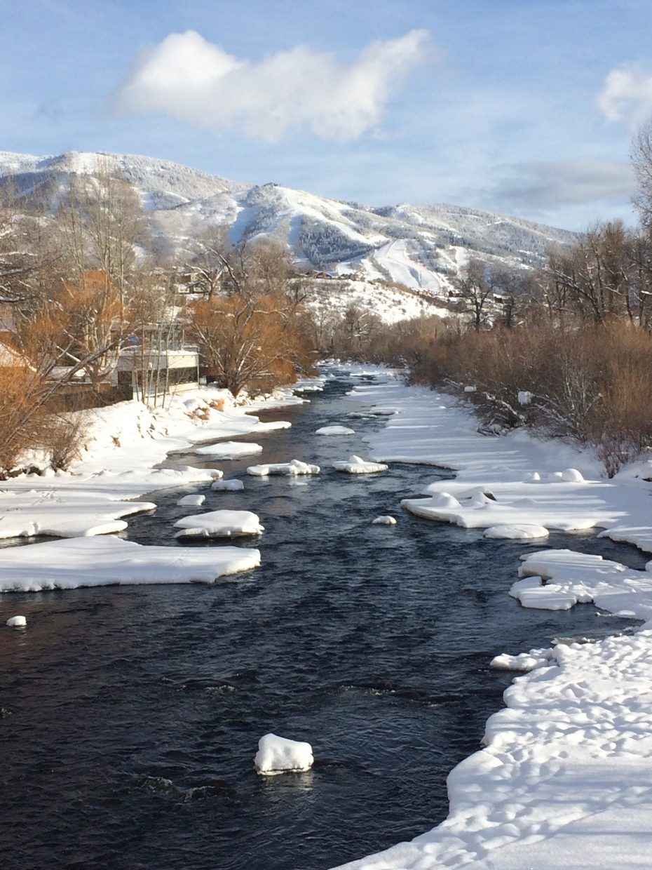 Mount Werner, covered in snow, stands tall above the Yampa River.