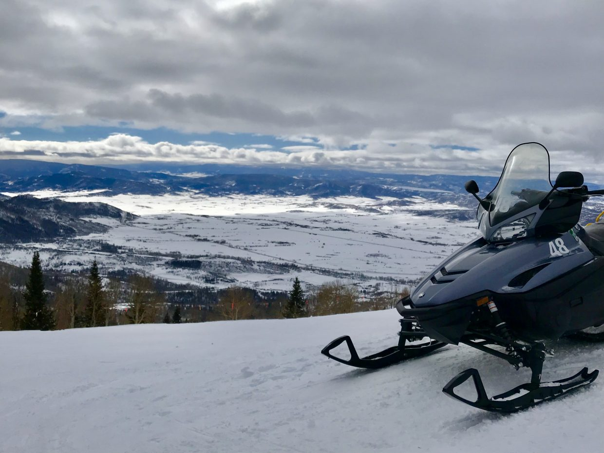 A snowmobile is parked overlooking the horizon.