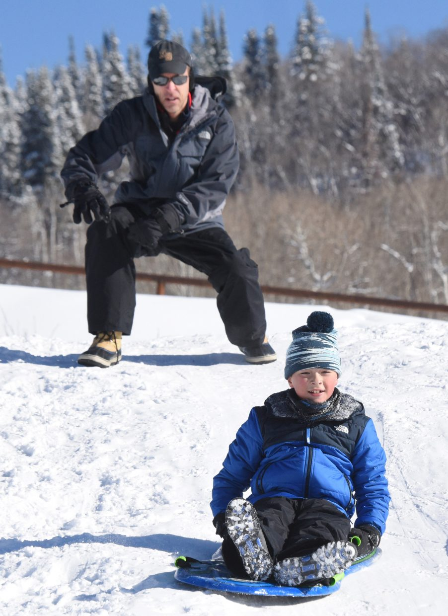 Reid Brusven gets a little push from dad, Eric while sledding with his family near the Steamboat Springs Middle School Wednesday afternoon.