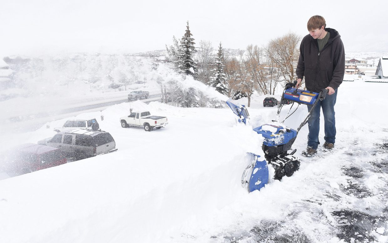 Patrick  Paulsen  uses a snowblower to clear the snow off the roof at Russell's Auto Salon in Steamboat Springs Friday morning.