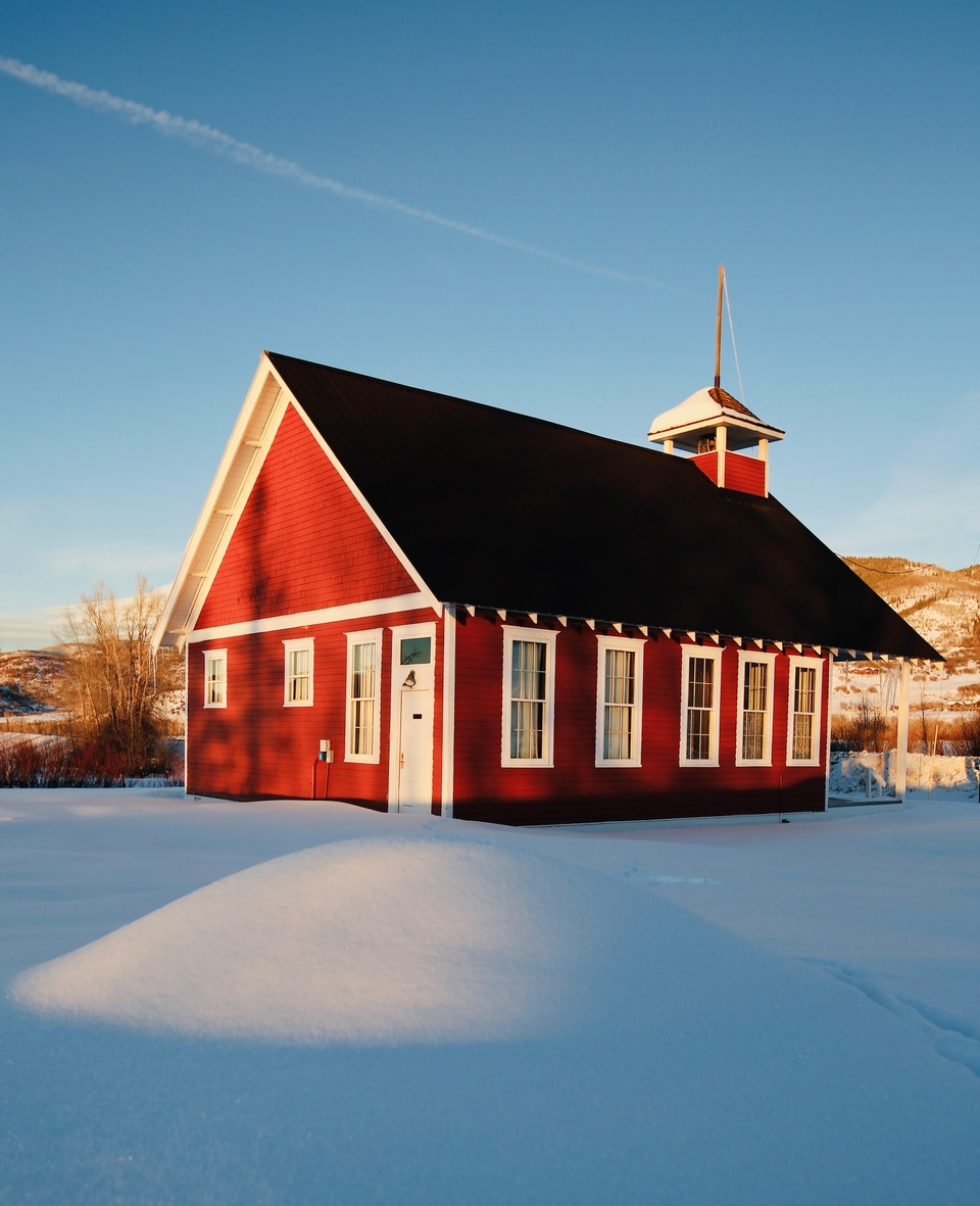 The sun sets over a red schoolhouse.