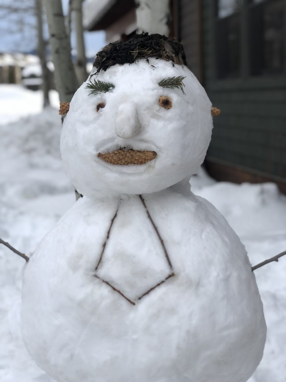 A business-attire snowman greets people.