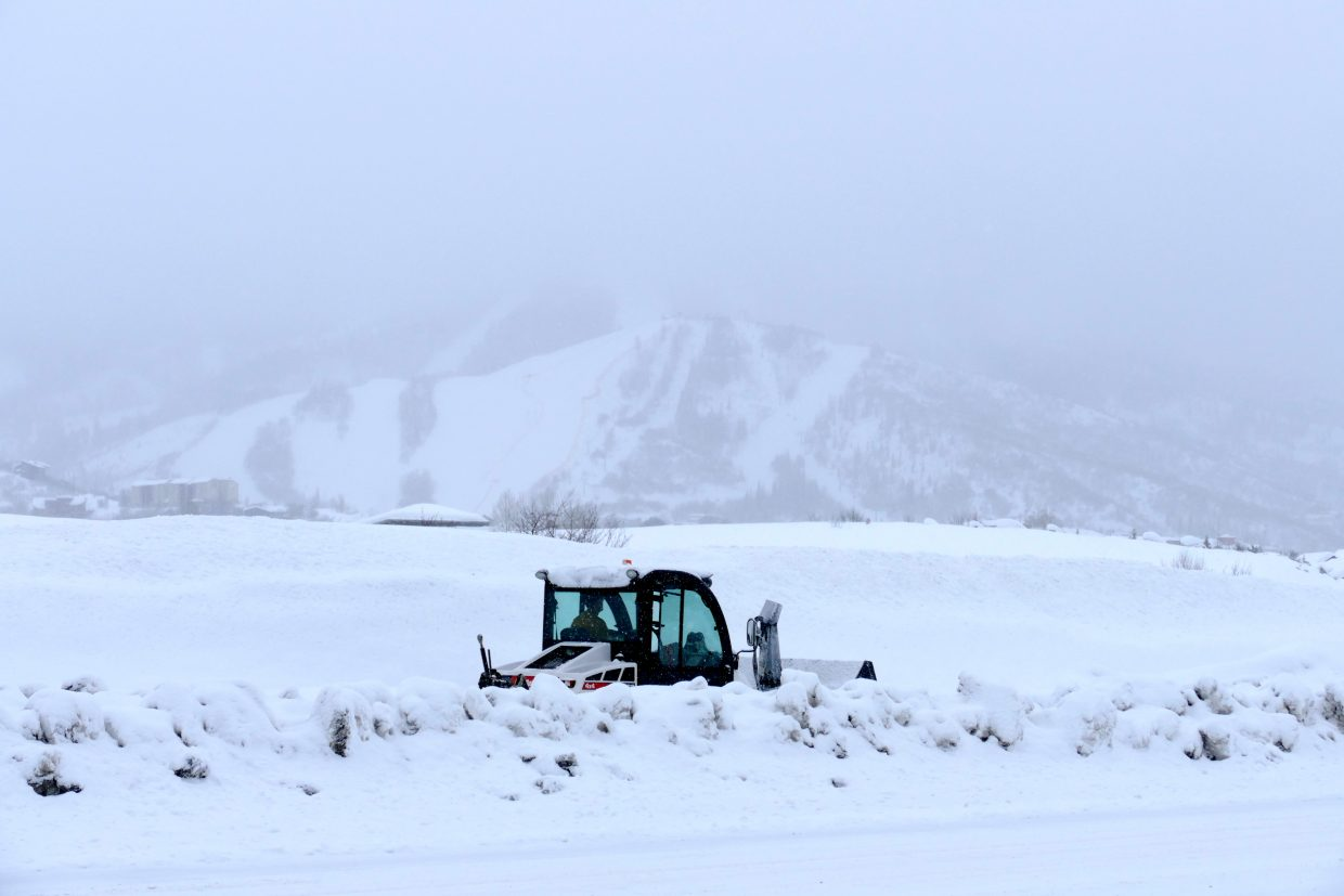 a little snowplow clearing the sidewalks with the slopes of the ski area in the background.
