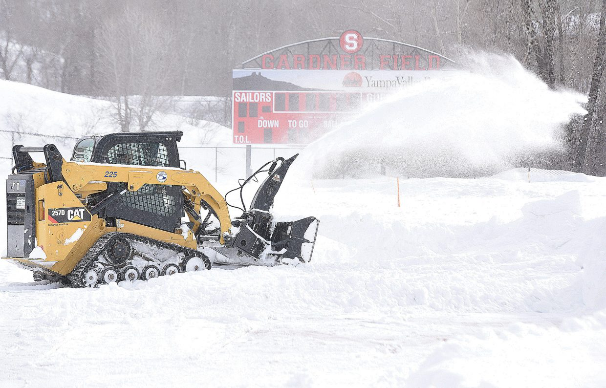 Dale Franks, an employee with Native Excavating, uses a snowblower to remove snow from the running track at Steamboat Springs High School Tuesday morning. Crews from Native are clearing the field an track, and crews from Flattop Excavations is shoveling the stands as the high school prepares for the start of the 'Spring