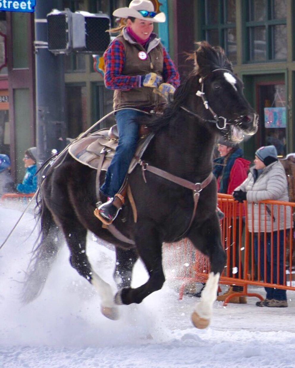 A cowgirl rides her horse down a snow-covered Lincoln Avenue during the 106th Winter Carnival.