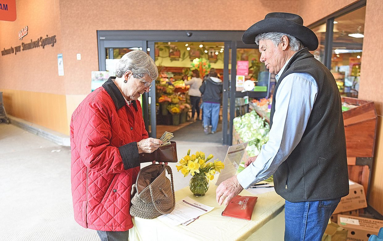 Scott Flower visits with Suzanne Wickham while selling daffodils at the entrance to City Market in Steamboat Springs. The proceeds from the sale of the flowers will benefit hospice services in Routt County.