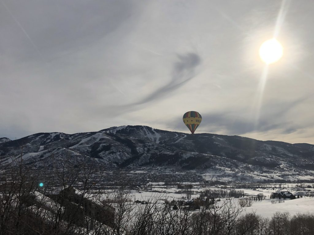 A hot air balloon looks as though it is sitting on the side of Mount Werner.