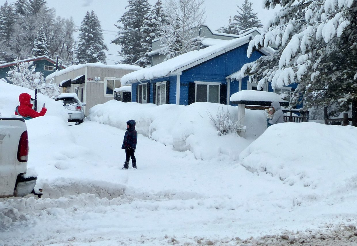 A family takes pictures of the tall snowbanks while walking along a snowy sidewalk in Steamboat Springs.