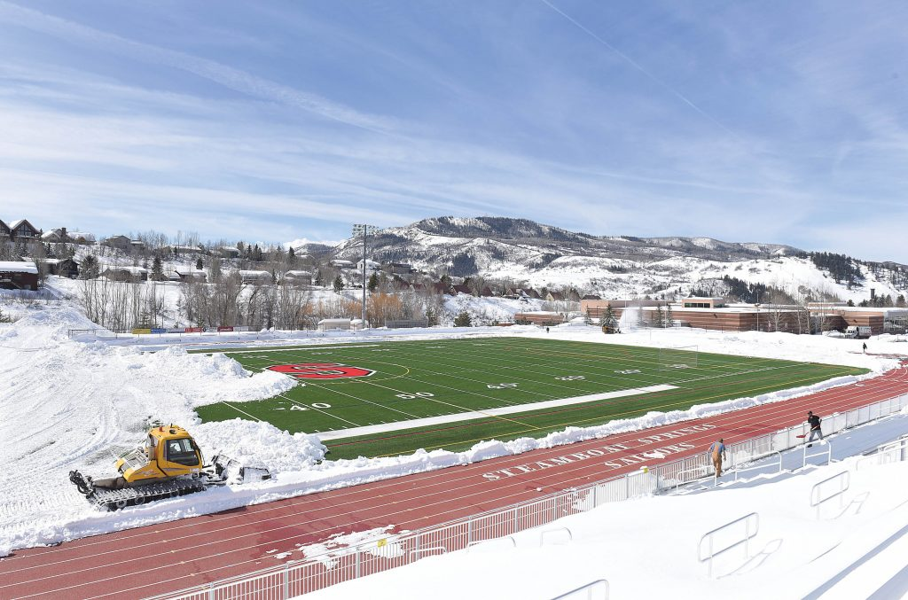 A groomer pushes snow off of Gardner Field Monday morning. This is the second time this spring that a groomer has been used to remove the snow from Gardner Field's artificial surface. The first attempt came last month during
