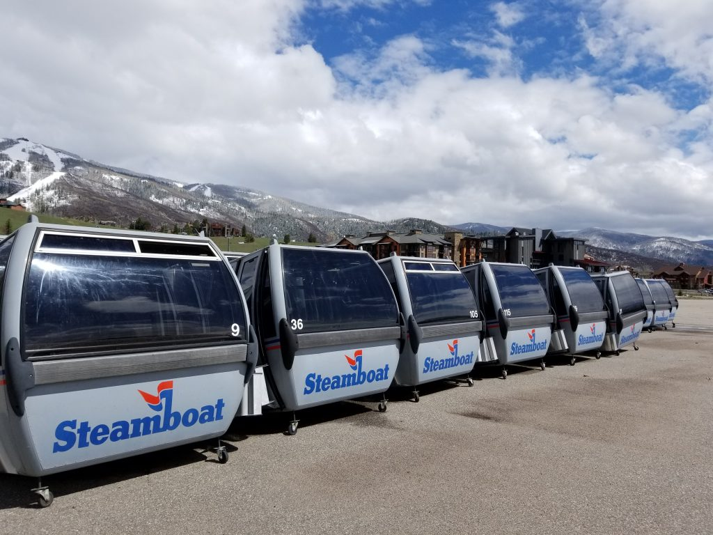 Old gondola cars are lined up in a row in Meadows Parking Lot.